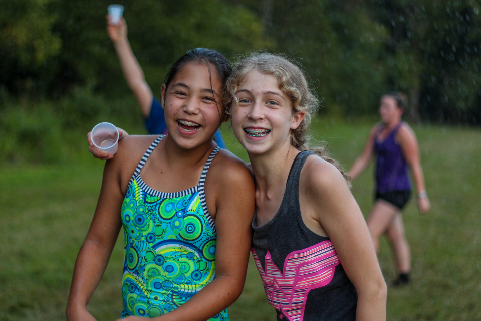 Two junior girl campers forget all about their phones as they take part in a massive water fight on our soccer field at Camp Friendship.