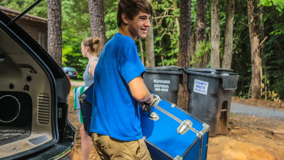 One of our Counselors In Training unpacks his blue trunk, perfect for storing all he needs for a overnight residential camp.