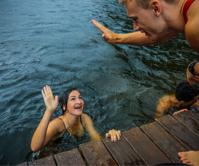 Teen girl camper and male counselor high five at Camp Friendship Lake