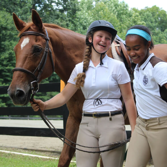 Two girls walking with horse at Camp Friendship Equestrian Center