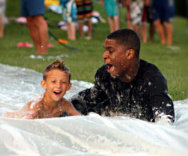 A junior boy camper speeds down our slip n' slide with his cabin counselor.