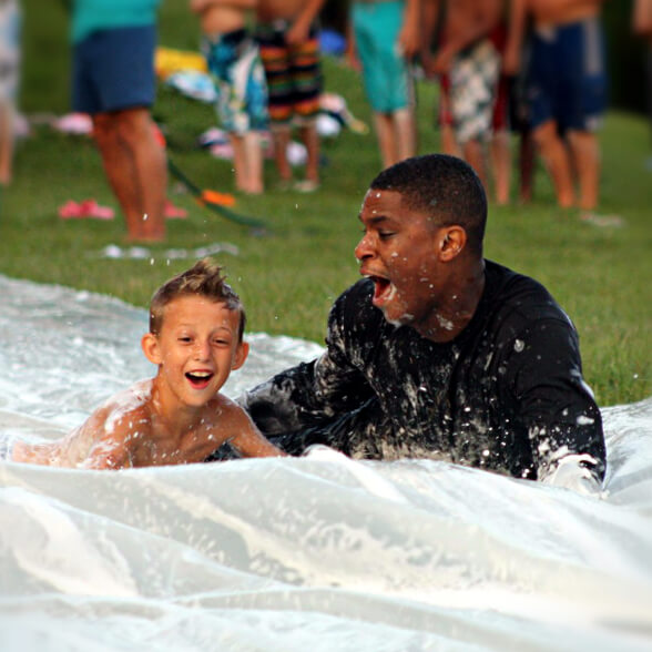 Camper and counselor at slip 'n slide evening activity