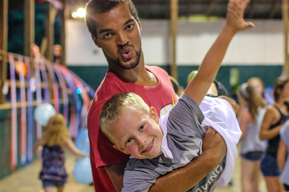 "A junior counselor helps his camper ""fly"" at the camp dance."