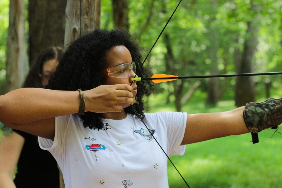 Teen girl camper fires an arrow at Camp Friendship's Archery Range in Virginia