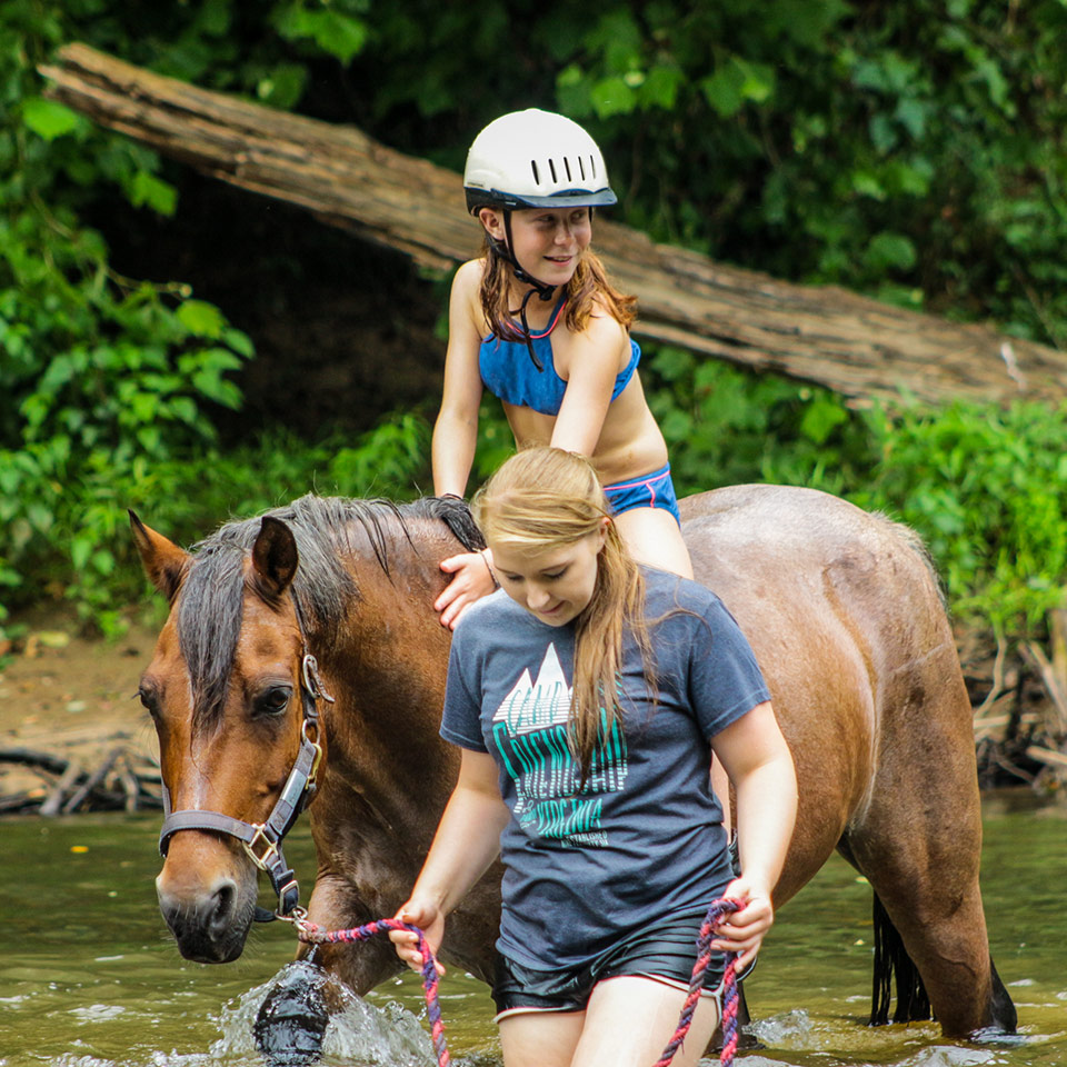 Camper and staff enjoy cooling off with a river ride on horseback at the Camp Friendship overnight camp in Virginia