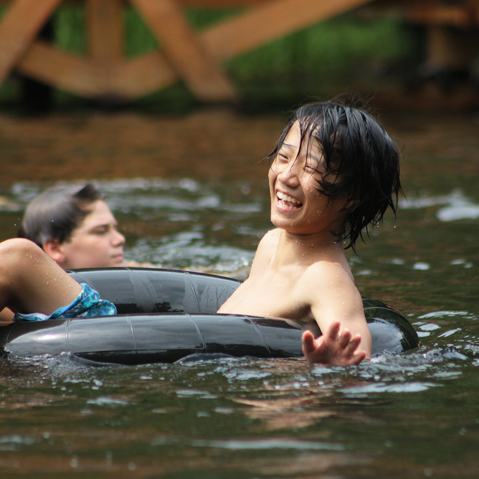 A senior village camper laughs as he sits in an inner tube floating through Friendship Lake.