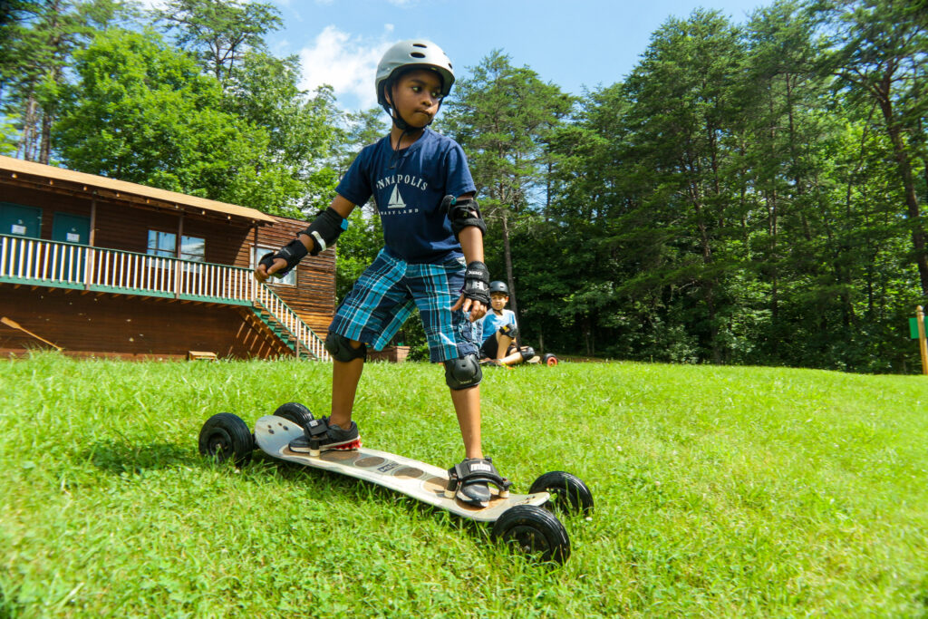 Young boy Mountain Boarding at an overnight camp