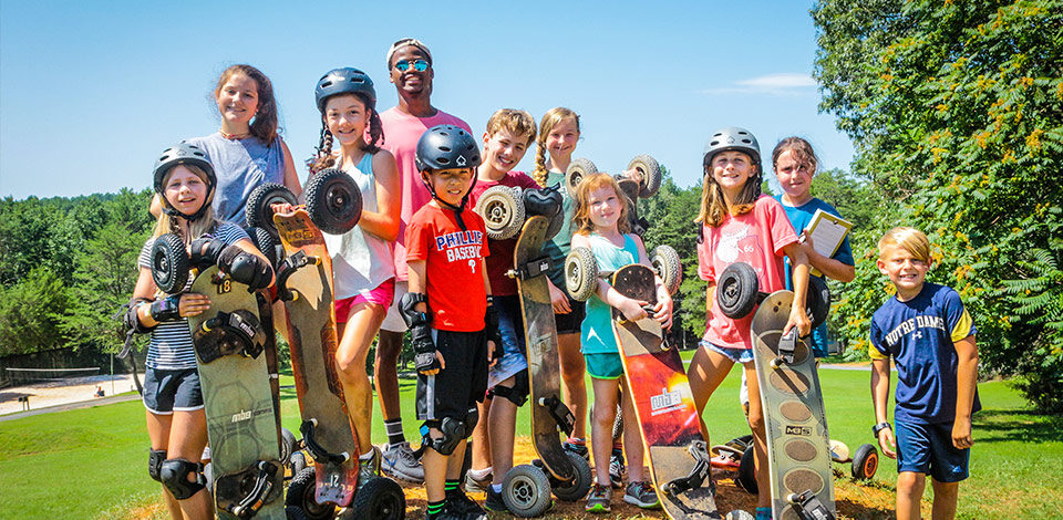 Campers and staff pose with the Mountain Boarding activity at Camp Friendship residential camp for kids and teens