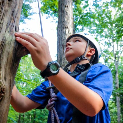Young boy camper climbs an element at the High Ropes activity at overnight camp in Virginia