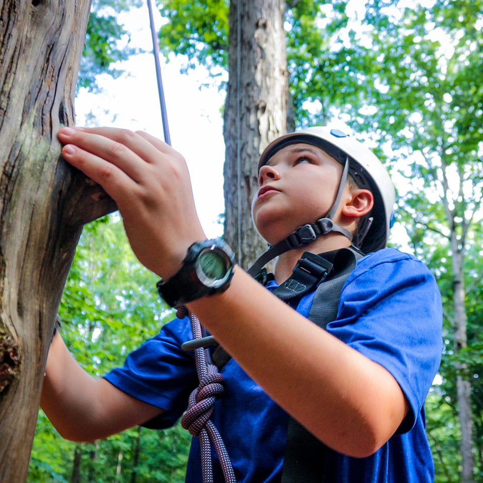 A teen camper challenges himself by climbing the pamper pole, one of our high ropes elements.