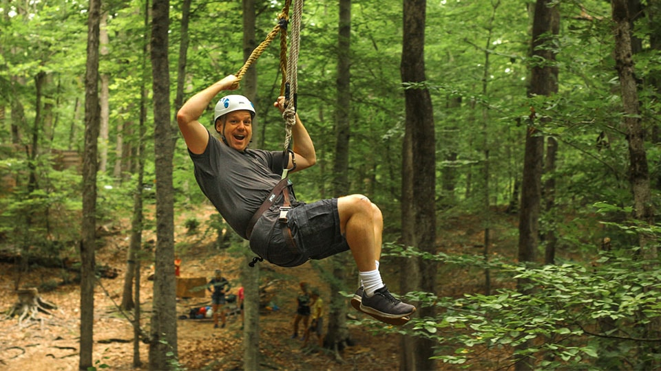 Adult family camper enjoys the zip line at Camp Friendship in Virginia