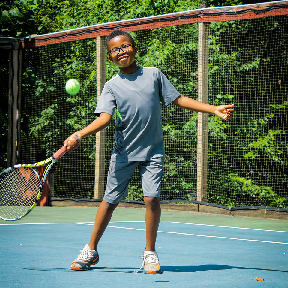 Young boy camper prepares to hit a tennis ball at overnight summer camp in Virginia