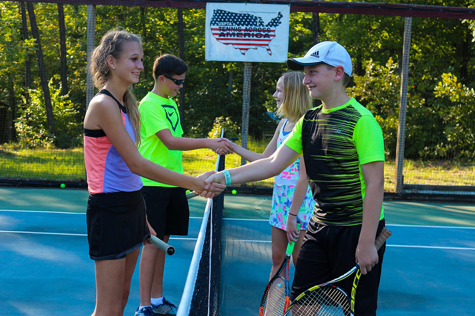 Coed campers shake hands after a tennis match at Camp Friendship summer tennis program