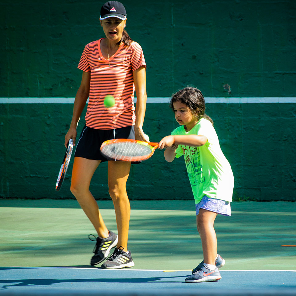 Female Tennis instructor teaches young girl how to hit a tennis ball at Camp Friendship