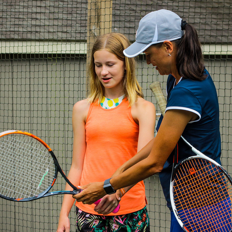 Female Tennis instructor shows teen camper how to hold a tennis racket at tennis summer camp in Virginia