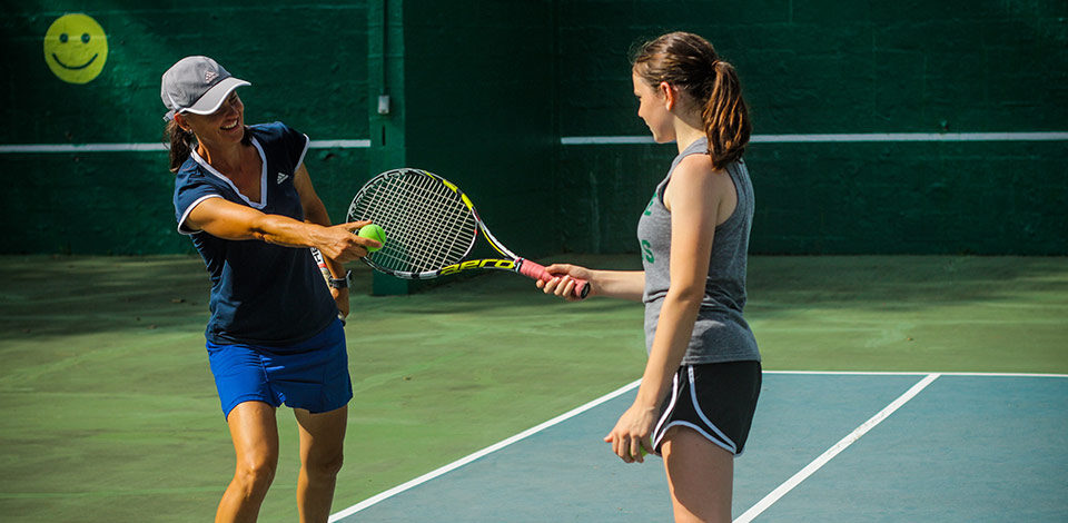 Female Tennis instructor teaches teen camper where to hit the ball on her racket