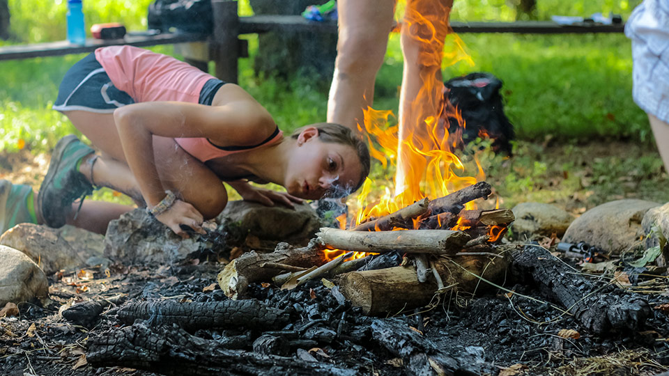 Girl Camper blows on campfire to keep it burning