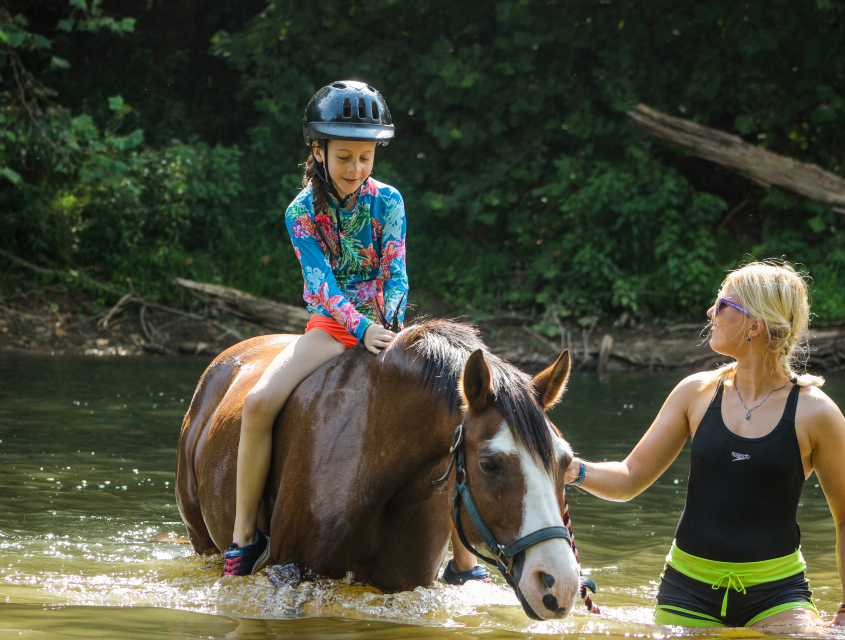 Girl camper riding a horse in the river assisted by a counselor at overnight summer camp in Virginia