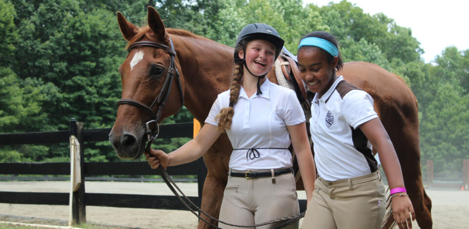 Two Equestrian campers walk with a horse at the Camp Friendship Horse Show