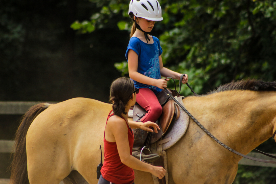 Staff member helps a camper with her horse at an overnight Equestrian Camp in Virginia