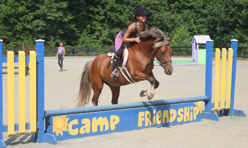 Equestrian Camper jumps with her horse at the Camp Friendship overnight horseback riding camp in Virginia