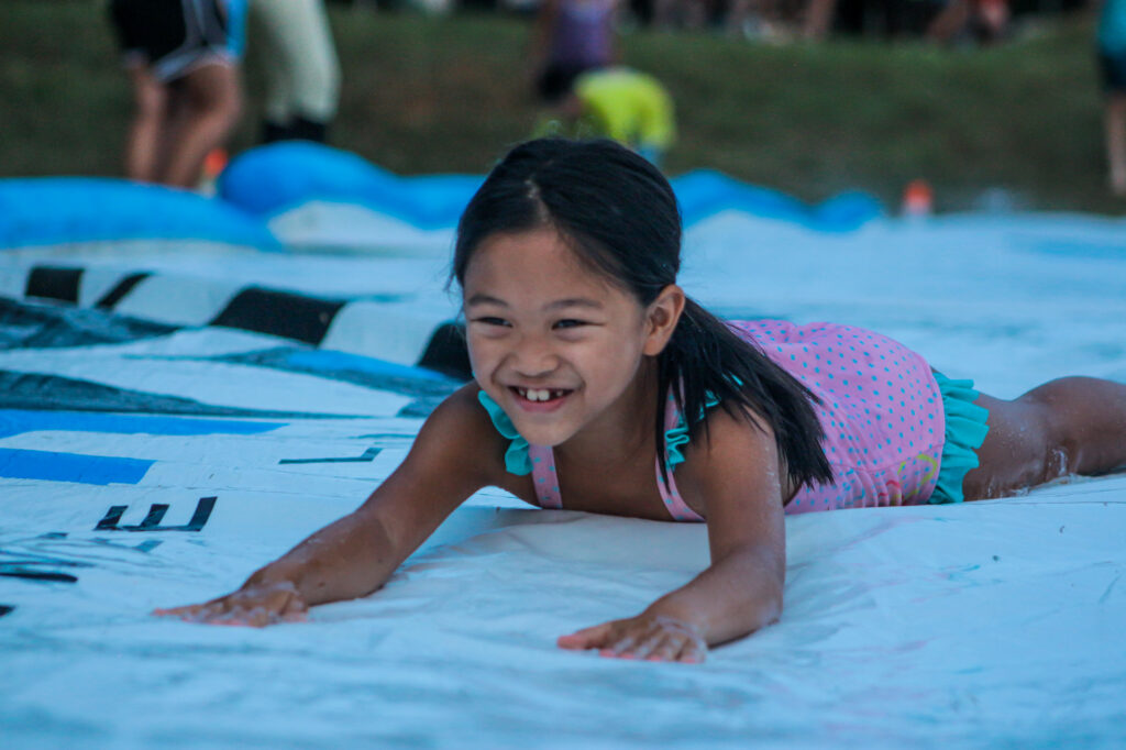 Junior Girl camper enjoying the Slip 'n Slide activity at Camp Friendship
