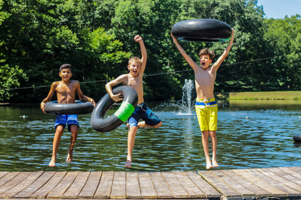 Three boy campers enjoy Friendship Lake at Camp Friendship