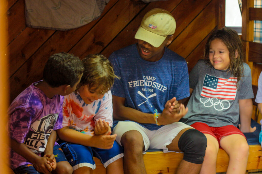 Three Junior Boy campers and a Counselor bonding during Village time