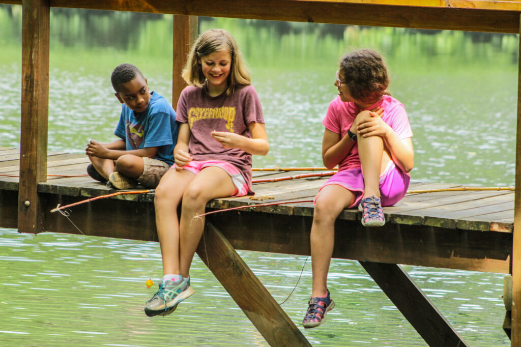 Junior campers dressed in clothes that can get wet are more than prepared for this fishing session by friendship lake.