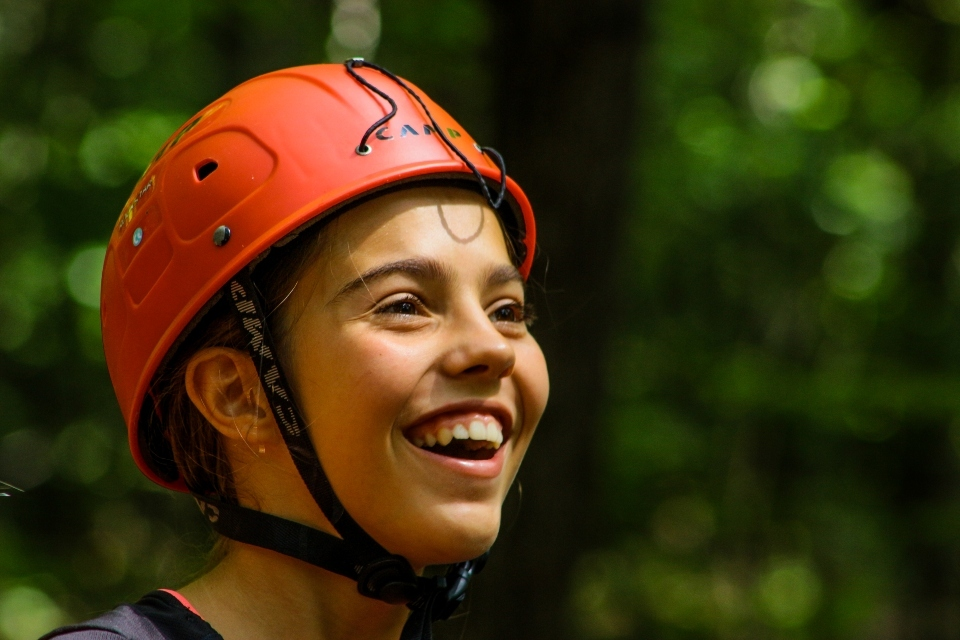 Teen Camper smiles while at the High Ropes course at a coed overnight camp in Virginia