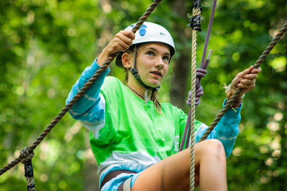 A teen camper performs a climb on her chosen high ropes element.