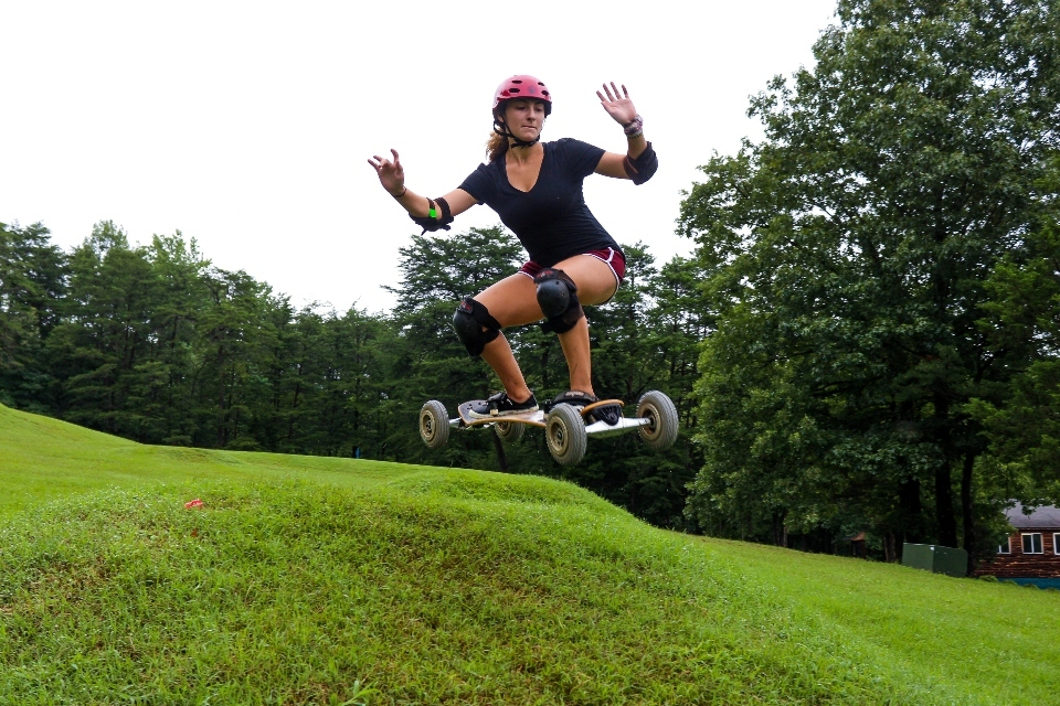 Senior Village girl camper jumps with her mountain board during an activity at Camp Friendship