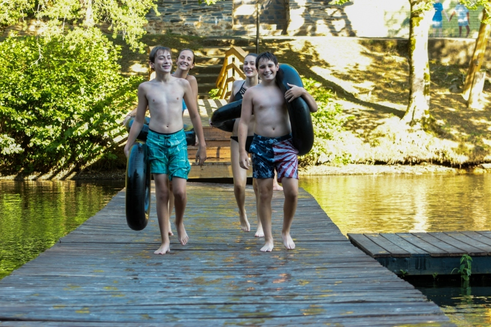 Teen boy campers walk on the floating dock at Friendship Lake at Virginia summer camp