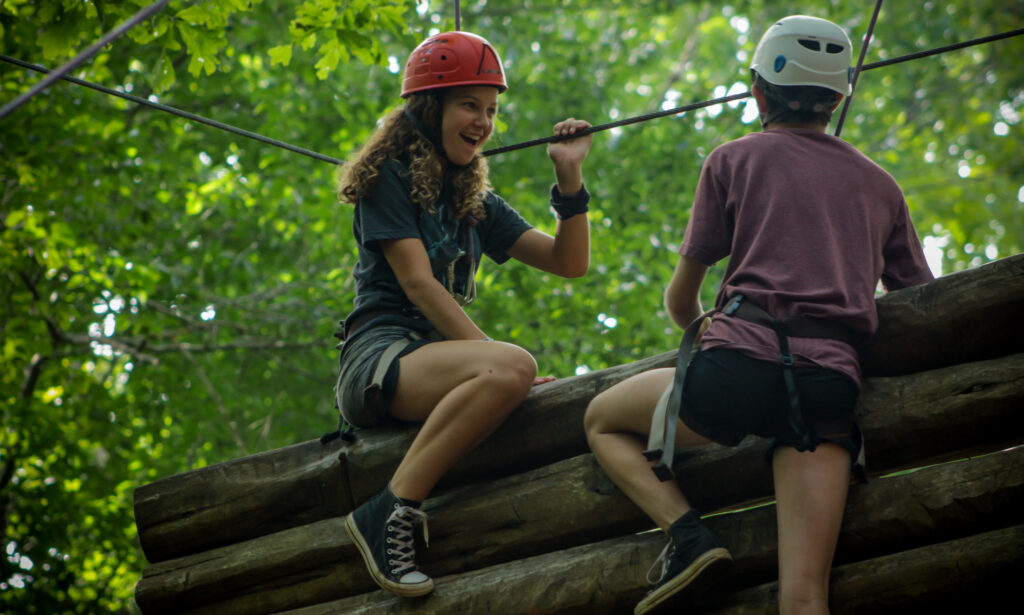 Two Senior Village girl campers conquer one of the High Ropes elements at a coed summer camp