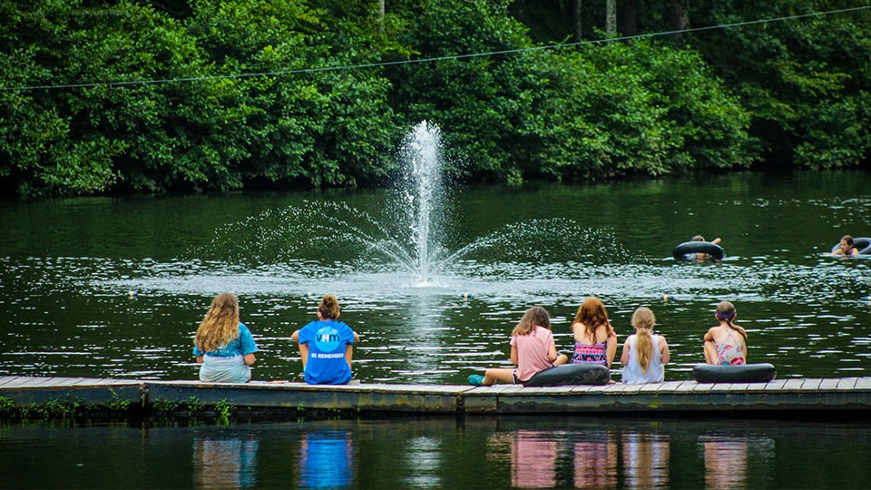 Campers on the lake dock in front of a fountain