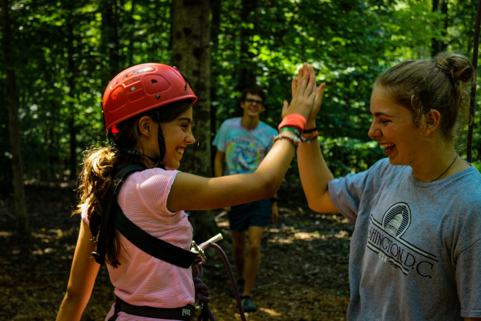 Counselor and camper giving a high five at the High Ropes Course at Camp Friendship residential camp