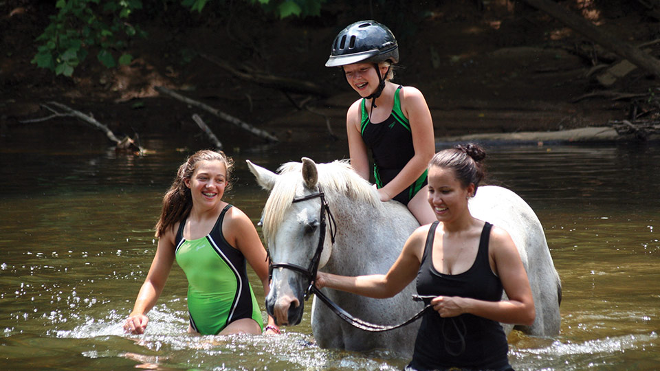 A camper and two counselors enjoy a river ride on horseback at Camp Friendship overnight Equestrian Camp