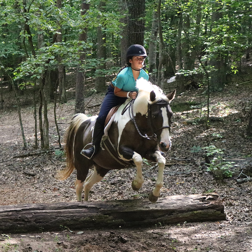 A girl Equestrian camper jumps her horse while on a trail ride at the Camp Friendship overnight horseback riding camp in Virginia