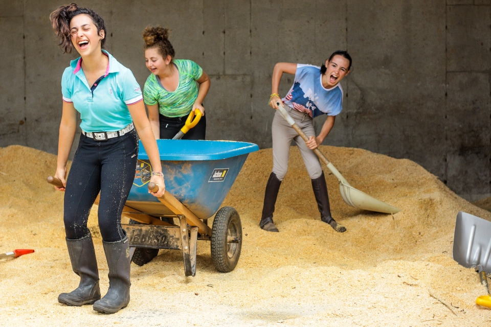 Three girls gather bedding for their horses' stalls at an overnight Equestrian camp as part of their barn chores.