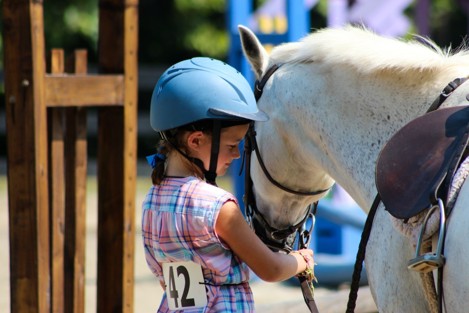 Young Equestrian camper walks with her horse at the Camp Friendship Horse Show