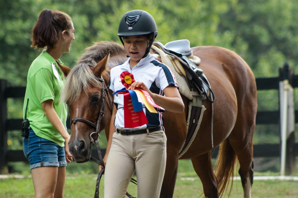 Young Equestrian camper looks at her ribbon after the Horse Show at the Camp Friendship overnight Equestrian program