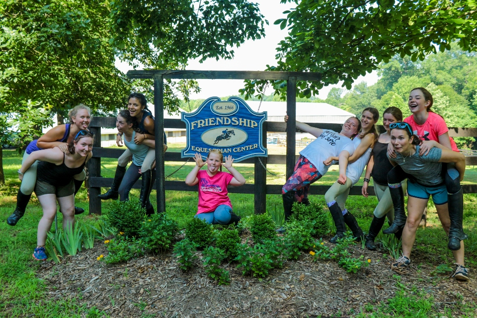 Equestrian Campers pose in front of the Equestrian Center sign at Camp Friendship sleep-away camp