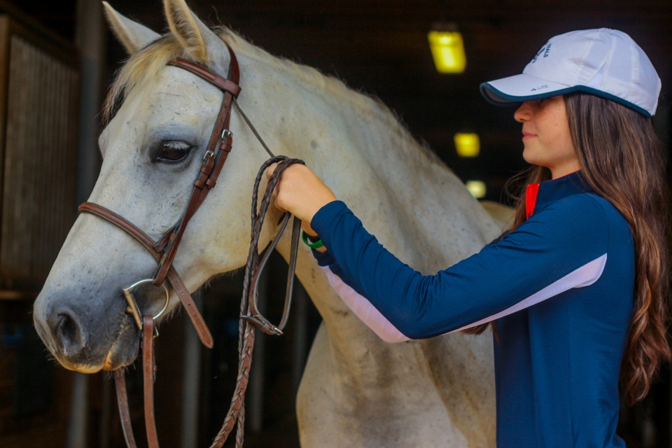 Equestrian camper puts a bridle on her horse at Camp Friendship Equestrian Center overnight camp in Virginia