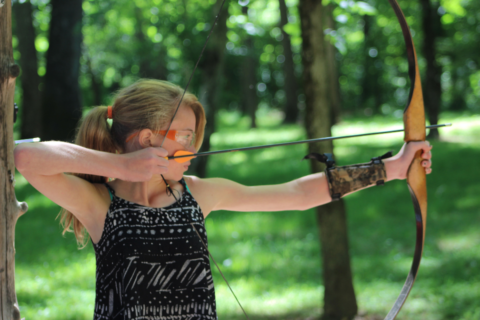 A junior camper pulls back a bow and aims for a bulls eye.