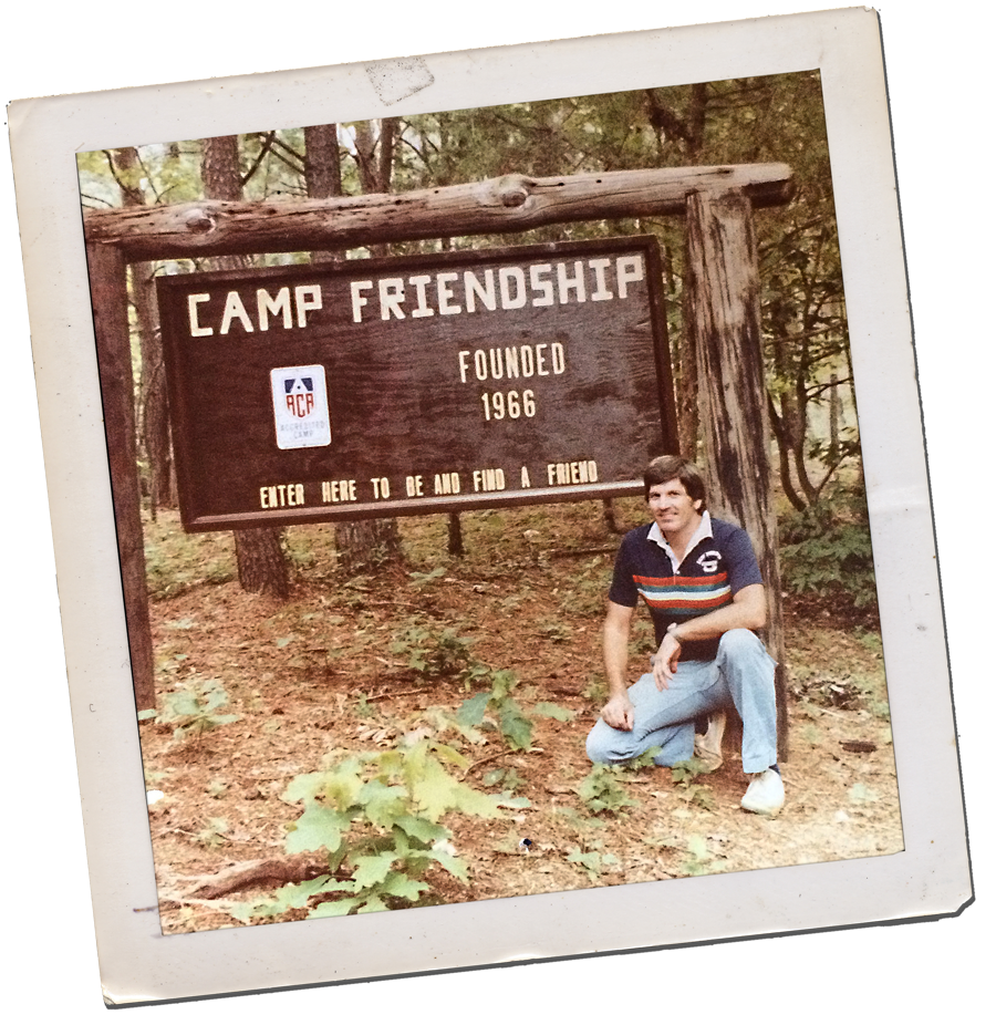 Camp Friendship founder Chuck Ackenbom in front of original sign in the 1960s