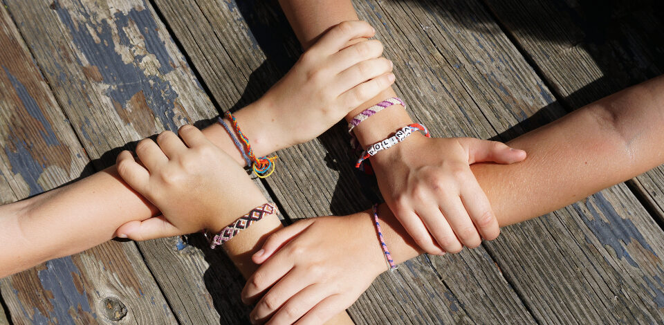 Four overnight campers clasp wrists to show off their friendship bracelets for their parents.