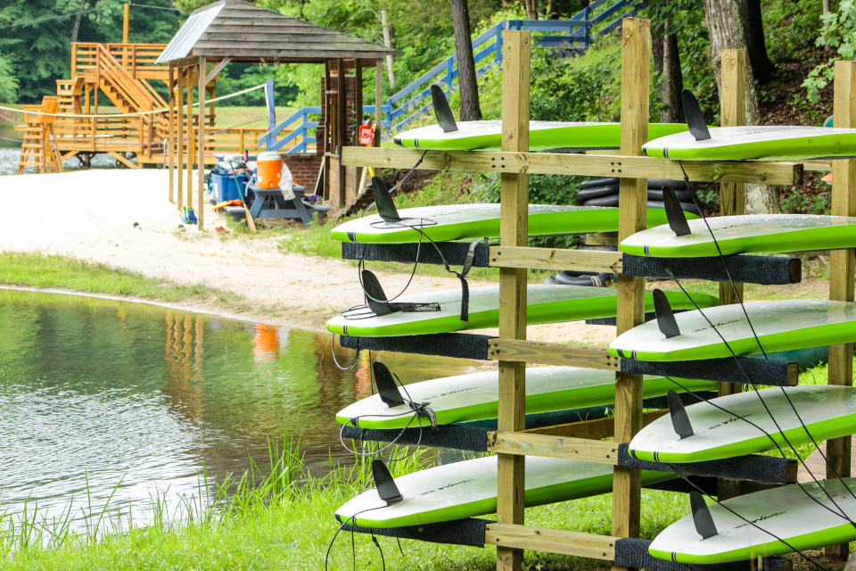 A rack of our green paddle boards stand ready to sail the water.
