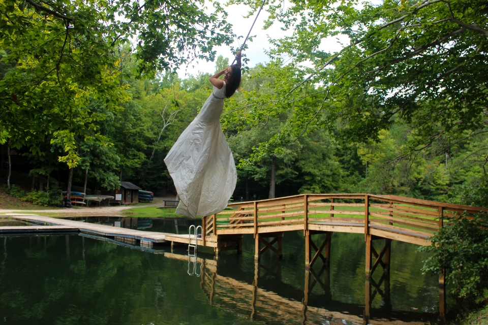 Bride in wedding gown swings over the water of Friendship Lake on rope swing