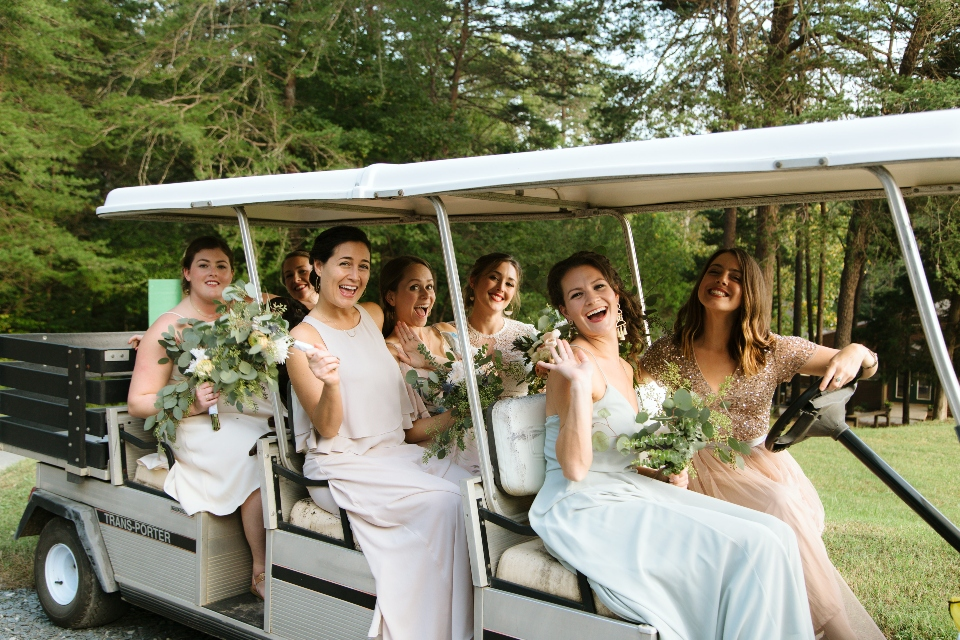 The bride and bridesmaids prepare to head to the ceremony in our stretch golf cart, availible for camp weddings and camp retreats.