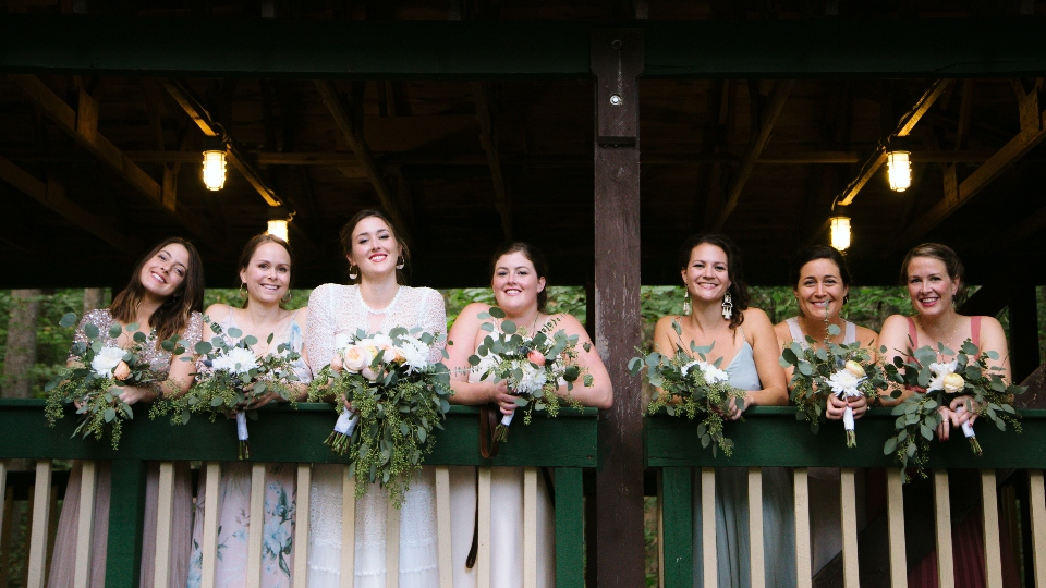 A bridal party poses with flowers in our dance pavilion as they prepare for a camp wedding ceremony.